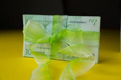 Pack of hundred euro banknotes with green bow-knot on yellow desk, gift or dividends concept, european union money. Pack of hundred euro banknotes with green bow royalty free stock image