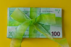 Pack of hundred euro banknotes with green bow-knot on yellow desk, gift or dividends concept, european union money. Pack of hundred euro banknotes with green bow stock photos