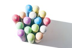 Pack of Jumbo Sidewalk Chalk, Assorted Colors, Bold Tips Casting Shadow on White Background. Top View.  royalty free stock photo