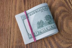 A pack of one hundred dollar bills stretched by an elastic band on a wooden table. A bundle of one hundred dollar bills stretched by an elastic band on a table Stock Image