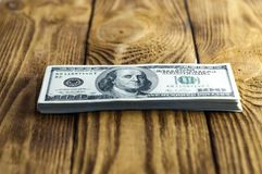 A pack of one hundred dollar bills on a wooden table. Small depth of field. Focus on the eyes of President Franklin. A pack of one hundred dollar bills on a Royalty Free Stock Images