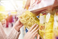 Pack of pasta in hands of buyer at store. Pack of pasta in the hands of the buyer at the store royalty free stock photography