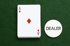 Pack Playing cards Ace Diamonds Poker dealer chip. Pack of playing cards showing the Ace of Diamonds with a dealers chip beside on a green baize background. Copy Stock Images
