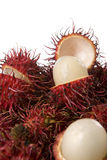A pack of rambutans with some. Aranging the rambutans against white background and some are opened to show its content Stock Photography