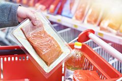 Pack of salmon in hand at store. Packing of salmon fish in the hand of the buyer at the grocery store stock photography