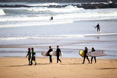 A pack of surfers enjoying their time at San Lorenzo beach during a sunny Easter morning. royalty free stock photography