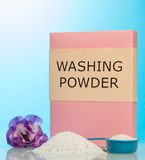 Pack washing powder in measuring cup, pile on blue background. Stock Photography