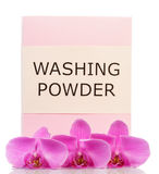 Pack of washing powder and orchid flowers isolated on white. Royalty Free Stock Photo