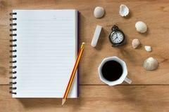 Packa ihop anteckningsboken med blyertspennan och radergummit som lägger på den bruna tabellen Royaltyfri Fotografi