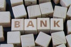 Packa ihop, financail- och pengarbegrepp vid kubträkvarteret med alfabetet som bygger ordet BANK på mitten på den mörka svart fotografering för bildbyråer