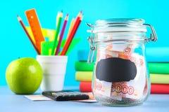 Packa ihop med ryska pengar, 5000 rubel och en räknemaskin, böcker på en grå bakgrund Finans moneybox, utbildning Arkivfoto