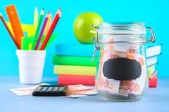 Packa ihop med ryska pengar, 5000 rubel och en räknemaskin, böcker på en grå bakgrund Finans moneybox, utbildning Royaltyfri Foto