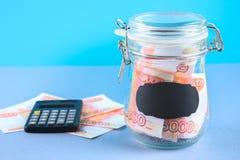 Packa ihop med ryska pengar, 5000 rubel och en räknemaskin på en grå bakgrund Finans moneybox, utbildning Royaltyfria Foton