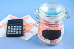 Packa ihop med ryska pengar, 5000 rubel och en räknemaskin på en grå bakgrund Finans moneybox, utbildning Fotografering för Bildbyråer