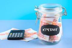 Packa ihop med ryska pengar, 5000 rubel och en räknemaskin på en grå bakgrund Finans moneybox, utbildning Text i ryss: krediterin Arkivfoton