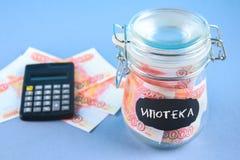 Packa ihop med ryska pengar, 5000 rubel och en räknemaskin på en grå bakgrund Finans moneybox, utbildning Text i ryss: mortgag Arkivfoto