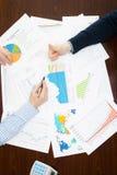 Packa ihop och att beskatta och all saker släkt med världen av finans - två affärsmän som gör överenskommelse över en tabell med  Arkivfoto