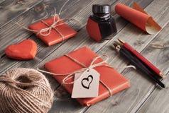 Packade gåvor, papper, kabel och etiketter på den bruna trätabellen Arkivbild