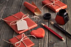 Packade gåvor, papper, kabel och etiketter på den bruna trätabellen Fotografering för Bildbyråer