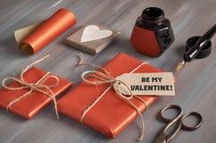Packade gåvor, papper, kabel och etiketter på den bruna trätabellen Royaltyfri Foto