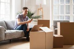 Packade kartonger med mannen som kallar hemsändning som flyttar sig Royaltyfri Bild