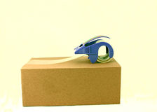 Package and blue tape dispenser Royalty Free Stock Photography