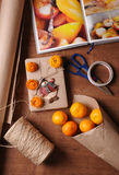 Package of christmas gift in kraft style. Tangerines, book, jute rope, paper roll, scissors, scotch on wood table Royalty Free Stock Images