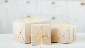 Package craft paper shop delivery box yellow twine. Packages wrapped in craft paper. shop goods delivery. three boxes tied with yellow twine royalty free stock images