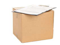Package delivery. Brown carton box with clipboard and package delivery form on white background Stock Image
