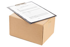Package delivery. Brown carton box with clipboard and package delivery form on white background Stock Photos