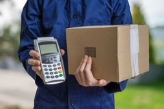 Package delivery concept. Man holds cardboard box and payment terminal. Package delivery concept. Man holds cardboard box and payment terminal in hands Royalty Free Stock Image