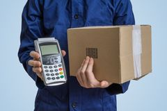Package delivery concept. Man holds cardboard box and payment terminal. Package delivery concept. Man holds cardboard box and payment terminal in hands Royalty Free Stock Photos