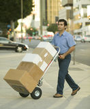 Package Delivery on Handtruck. Hispanic delivery man walking on city sidewalk with hand truck full of boxes to deliver Stock Photos