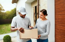 Package Delivery. Man Courier Delivering Box To Woman At Home. Female Receiving Parcel Outdoors, Signing Documents. High Resolution stock images
