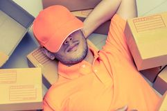 Package delivery person sleeping around boxes. Package delivery person sleeping around order boxes Royalty Free Stock Photo