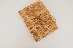 Stylishly packed package in the old newspaper. The package is framed with love, and packed with showers Royalty Free Stock Images