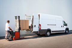 Package loading, the shipment has been processed in the parcel center. Courier is loading the van with parcels Stock Images