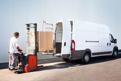 Package loading, the shipment has been processed in the parcel center. Courier is loading the van with parcels Stock Photo
