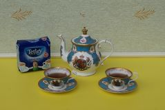 A package of original English Tetley`s teabags next to English teacups with saucers and teapot, fine bone china porcelain royalty free stock image