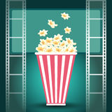 Package with popcorn and and film strip. Package with popcorn in dark movie theater with luminous screen and film strip Royalty Free Stock Photo