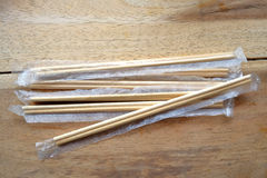 Package of readymade bamboo chopsticks on wooden background Royalty Free Stock Photo