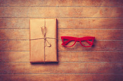 Package and red glasses on wooden table. Stock Photos