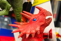 Package of toy dinosaurs with one red triceratops dino head featured - selective focus royalty free stock images