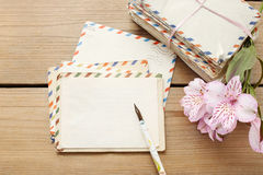 Package of vintage letters, pen and pink alstroemeria flowers Stock Photos