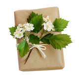 Package wrapped in kraft paper and tied with a rope and flowers Stock Photography