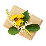 Package wrapped in paper and tied with a rope and bouquet of flo Stock Image