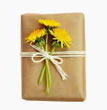 Package wrapped in paper and tied with a rope and flowers Stock Photo