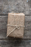 Package wrapped in wrinkled brown paper lying on weathered wood Stock Photo