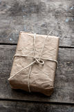 Package wrapped in wrinkled brown paper lying on weathered wood Stock Images