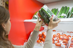 Packaged cucumber with woman hand in the supermarket Royalty Free Stock Photo